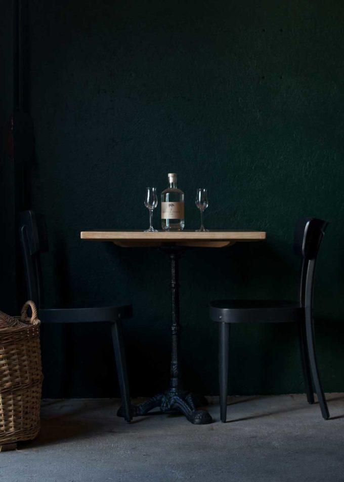 Distillerie Porrentruy Bouteille sur table et chaises