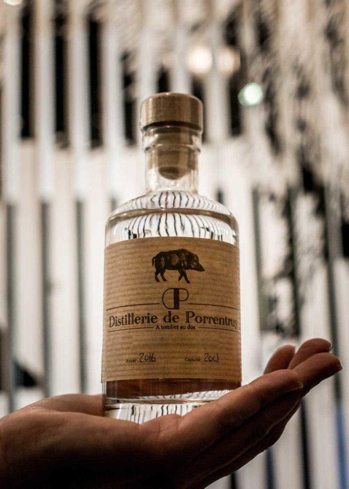 distillerie porrentruy bouteille dans la main